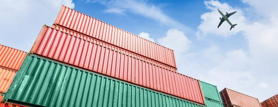 Stack of containers with cargo plane flying overhead